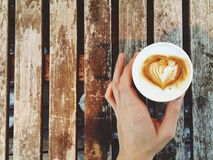 Вынос кофейной чашки на деревянной таблице Стоковое Фото