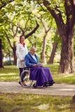 Вынянчите нажатие пожилого человека в кресло-коляске пока книга чтения Стоковое Фото
