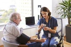 Вынянчите носить Scrubs в офисе проверяя старшее мужское кровяное давление пациентов стоковая фотография