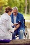 Вынянчите оценку человека кровяного давления пожилого в кресло-коляске Стоковая Фотография RF