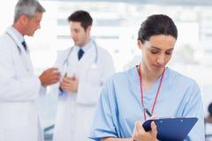 Вынянчите сочинительство на доске сзажимом для бумаги пока доктора говорят совместно Стоковое Изображение RF