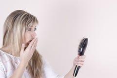 Выпадение волос Подавленная молодая женщина смотря ее щетку для волос и выражая негативизм стоковое фото rf