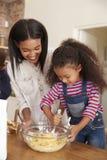 Выпечка матери и дочери испечет в кухне совместно Стоковое Фото