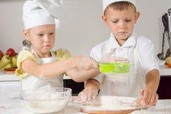 Выпечка мальчика и девушки в кухне Стоковые Фотографии RF