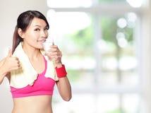 Выпивать и большой пец руки девушки спорта вверх стоковое изображение