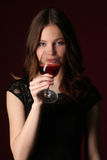 выпивая вино девушки конец вверх темнота предпосылки - красный цвет Стоковое Изображение RF