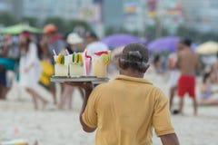 Выпивая коктейли caipirinha, caipifruta и othe тропические на пляже Copacabana в поставщиках Рио-де-Жанейро Бразилии на пляже Ipa стоковое изображение rf