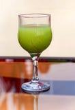 Выпивая стекло с зеленым напитком стоковые фотографии rf