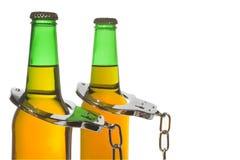 Выпитые пиво и наручники - управляющ принципиальной схемой стоковое изображение rf