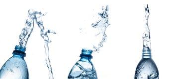 Выплеск бутылки с водой изолированный на белизне стоковые фотографии rf