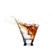 Выплеск вискиа из стекла изолированного на белой предпосылке Стоковое Изображение