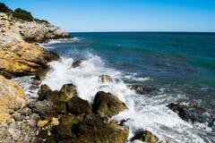 Выплеск воды на скалистой береговой линии Стоковые Фото