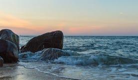 Выплеск волны в море против камня Стоковые Изображения RF