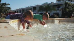 Выплеск мальчика и девушки в фонтане взрослые молодые сток-видео