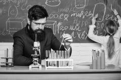 Выполнять эксперимент Учитель и зрачок Мужской учитель давая урок в классе науки Публика или частная школа стоковые изображения rf