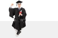 Выпускник колледжа держа диплом усаженный на панель Стоковое Фото
