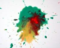 Выплеск акварели в зеленых желтых красных оттенках на белой предпосылке Стоковые Фото