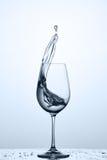 Выплеск более чистой воды из рюмки пока стоящ на стекле с капельками против светлой предпосылки стоковое фото rf