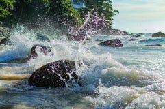 Выплеск волны в море против камня Стоковая Фотография