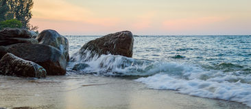 Выплеск волны в море против камня Стоковые Изображения