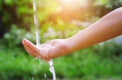 Выплеск воды лить в предпосылке руки и природы стоковая фотография