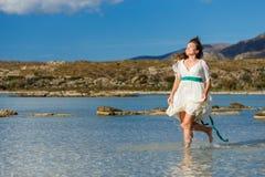 Выплеск воды и красивого хода девушки Стоковая Фотография