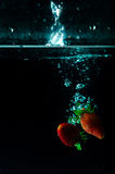 Выплеск воды клубники на черной предпосылке Стоковое фото RF