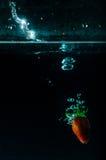 Выплеск воды клубники на черной предпосылке Стоковое Изображение RF