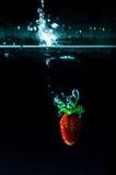 Выплеск воды клубники на черной предпосылке Стоковые Изображения
