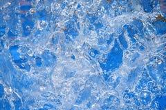 Выплеск воды на голубой предпосылке Стоковые Фото