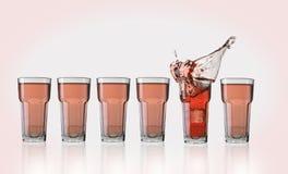 Выплеск коктеиля с кубом льда на розовой предпосылке Стоковая Фотография RF