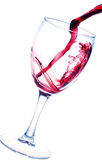 Выплеск красного вина в стекле изолированном на белизне Стоковая Фотография