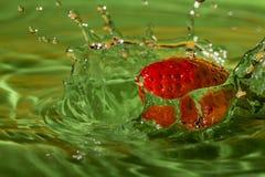 Выплеск клубники с зеленой предпосылкой Стоковое Изображение