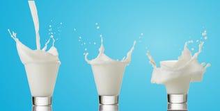 Выплеск молока от стекла на голубой предпосылке Стоковые Фотографии RF