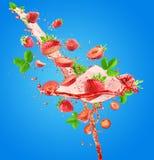 Выплеск сока клубники на голубой предпосылке Стоковое Изображение RF