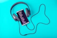 Выравниватель на экране телефона при наушники играя музыку на голубой предпосылке Стоковые Изображения RF