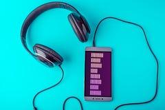 Выравниватель на экране телефона при наушники играя музыку на голубой предпосылке Стоковое фото RF