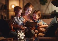 Выравнивать чтение семьи мать читает детей книга перед идти положить в постель стоковое фото rf