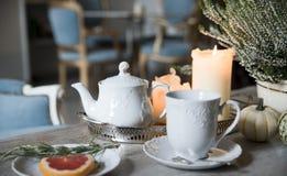 Выравнивающ чай с розмариновым маслом и грейпфрутом, светом горящей свечи в винтажном кафе стоковое фото rf