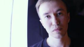 Выражения лица кавказского человека в нижнем свете Тайна молодого человека предпосылки темноты белая выделенная видеоматериал