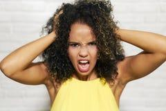 Выражения лица молодой чернокожей женщины на кирпичной стене Стоковые Фото