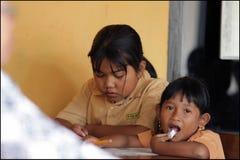 Выражения маленькой девочки на временной школе в казармах опорожнения после извержения горы Merapi Стоковое Изображение RF