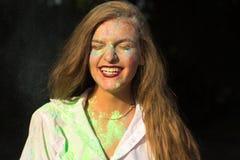 Выразительная молодая женщина в белой рубашке празднуя фестиваль Holi Стоковая Фотография