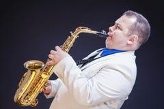 Выразительный зрелый кавказский мужской игрок саксофона представляя в белой сюите стоковая фотография rf