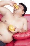 Выразительная тучная персона есть бургер Стоковое фото RF