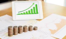 Вырастите вверх стог монеток с делом и профинансируйте экран диаграммы на Ла стоковое изображение