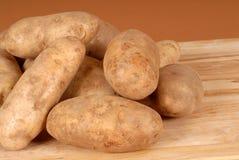 вырезывание доски сложило russet картошек несколько стоковая фотография rf