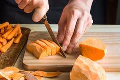 Вырезывание молодой женщины с сладким картофелем ножа в клин, корки на деревянной таблице, отрезало морковей Стоковое Изображение RF