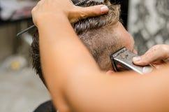 Вырезывание парикмахера и волосы моделирования электрическим триммером Стоковые Фотографии RF
