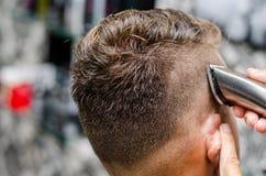 Вырезывание парикмахера и волосы моделирования электрическим триммером Стоковые Изображения